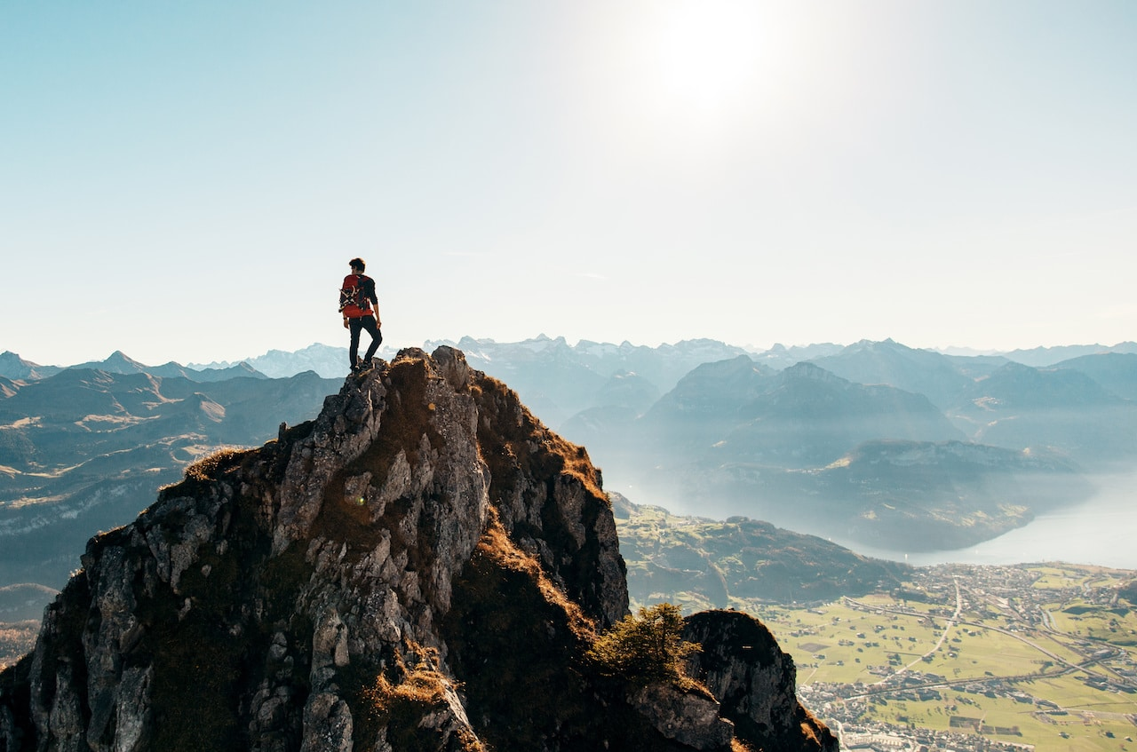 A man standing on a peak of a mountain.