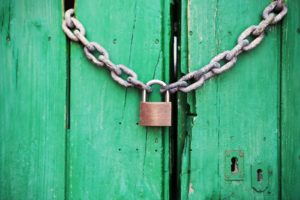 A padlock on a green wooden door